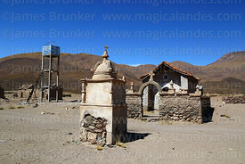 Rustic cairn, church and water storage tank in Churacari village, Bolivia