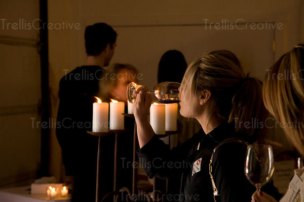A young woman drinking wine by candlelight