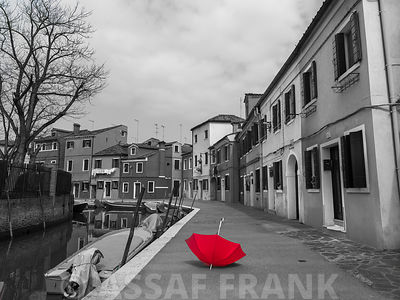 Red umbrella and a row of houses next to a canal, Burano, Italy