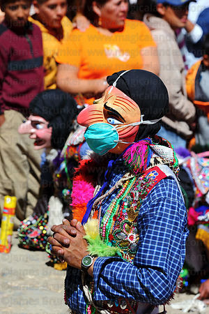 Masked Maqtas dancer wearing swine flu mask kneeling outside church during mass at Virgen del Carmen festival , Paucartambo , Peru