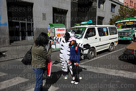 A woman takes a photo of her daughter with a zebra on a pedestrian crossing, La Paz, Bolivia