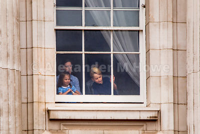 Princess Charlotte and her brother Prince George watching the RAF100 celebration crowds from a Buckingham Palace window