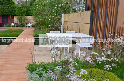 Terrasse contemporaine, mobilier de jardin : table et chaise collection Japan (Fabricant Estudi Hac), Massif fleuri : Anthriscus sylvestris 'Ravenswing', Allée en bois exotique Iroko. Paysagiste : Robert Myers, CFS, Angleterre