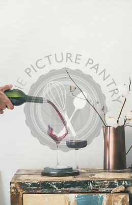 Red wine pouring from bottle into glasses, copy space