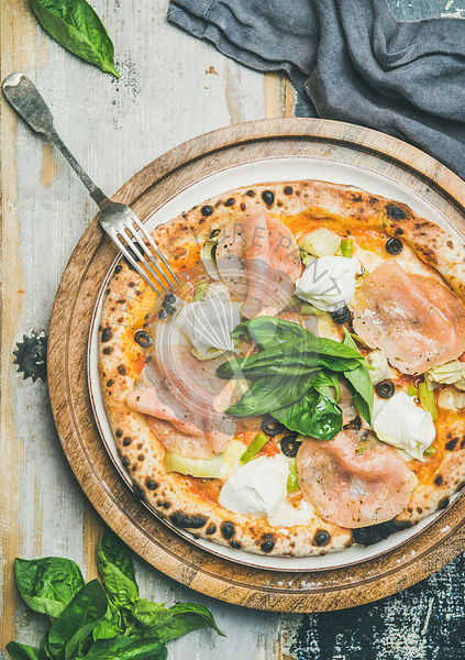 Freshly baked pizza with ham, artichokes, cheese and basil