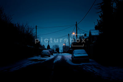 An atmospheric image of a sleepy, snow covered street a dawn.