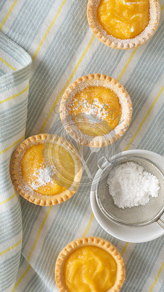 Small lemon tartlets dusted with powdered sugar.
