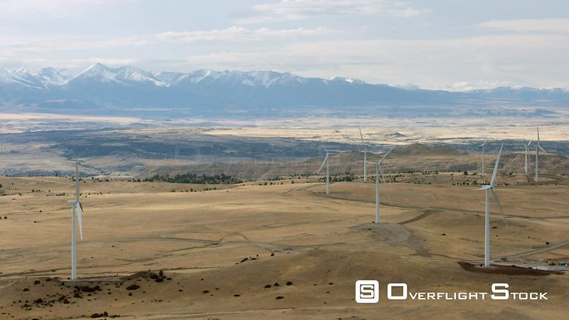 Golden plains sit in the shadow of the snow-capped Beartooth mountain Range in southwestern Montana. A group of wind turbines are perched in the foreground