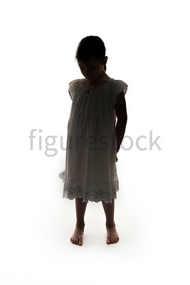 A Figurestock image of a little girl, in silhouette, in a night dress, looking down – shot from eye level.