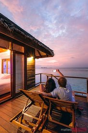 Couple watching sunset from bungalow, Maldives