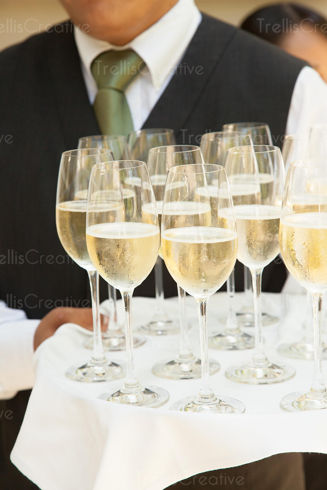 Waiters holding trays of chilled sparkling wine and champagne at a party