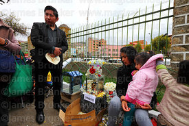 Family with skull of their dead child in cemetery, Ñatitas festival, La Paz, Bolivia