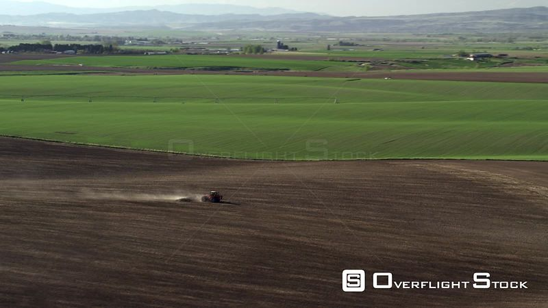 A tractor plows a field among the spring Green rolling foothills and farmland near Bozeman, Montana