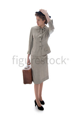 A 1940's / 1950's woman in a suit and hat, standing with a suitcase – shot from eye-level.
