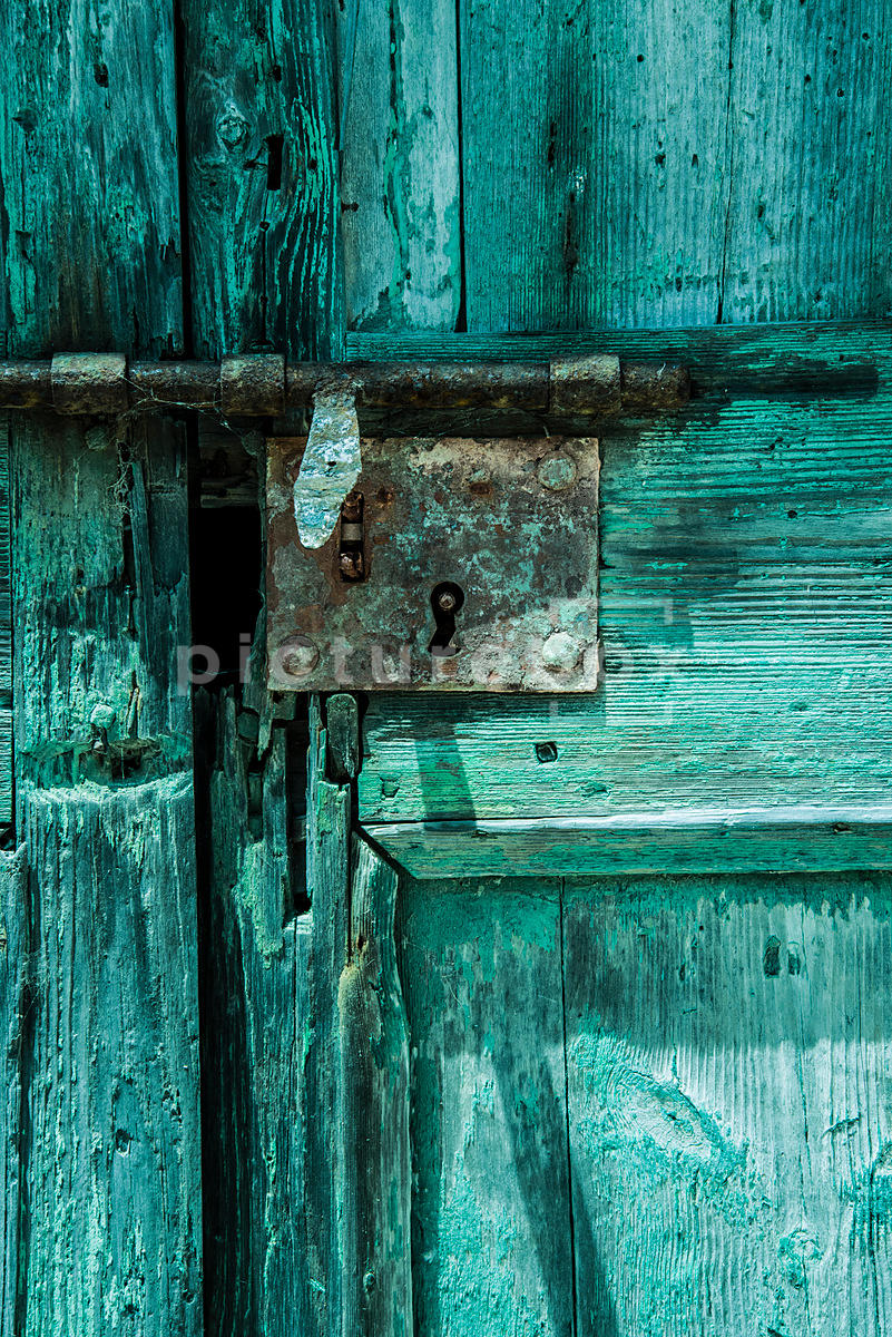 A rusted lock on a characterful old woodern door.