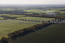 Farming landscape aerial photograph looking over green fields and tree lined farm roads and autumnal colours