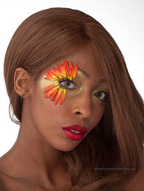 African American woman with light hair and flower around one eye. Studio.