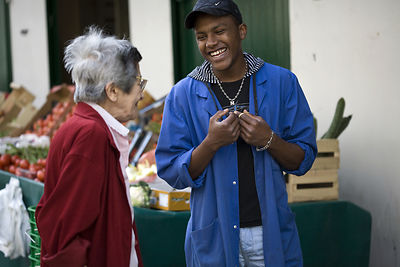 France - Paris - A shop assistant jokes with an elderly customer on the Rue Mouffetard.