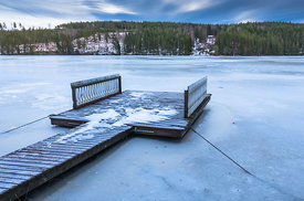 Jetty in frozen lake with forest in the background