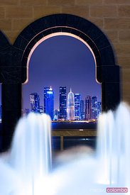 Qatar, Doha. Cityscape at night framed in a arch