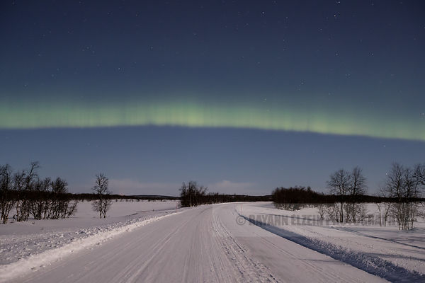 The Northern Lights shine strong despite the full moon above a road near Inari