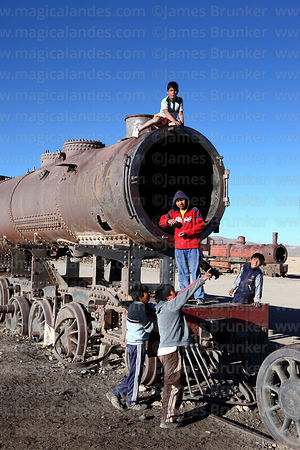 Local lads hanging out on old steam train in train cemetery, Uyuni, Bolivia