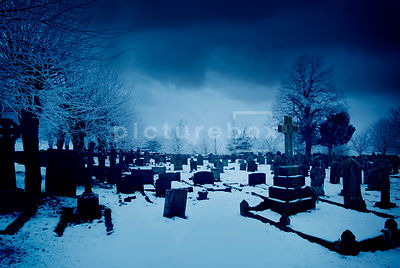 An atmospheric image of tombstones in a old, snow covered church graveyard at dawn.