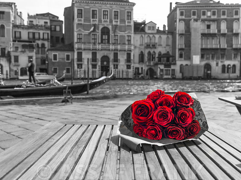 Bunch of red roses on street cafe table near canal, Venice, Italy