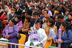Hosting family (alferado) holding figure of baby Jesus and candles during central mass for the Virgen de la Candelaria festival, Puno, Peru