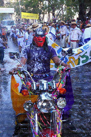 Biker covered in shaving foam and wearing devil mask at carnival parade, Tarija, Bolivia