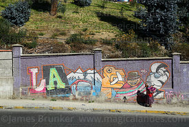 Aymara woman walking past mural with symbols of La Paz, Bolivia