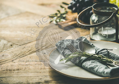 Plate with linen napkin, fork, spoon, candle holder, grapes on board, buns, olive tree branch over wooden background