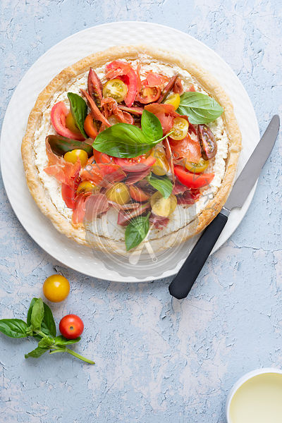 Round tart filled with cherry tomatoes, pancetta, feta cheese and basil on a plate with a knife.