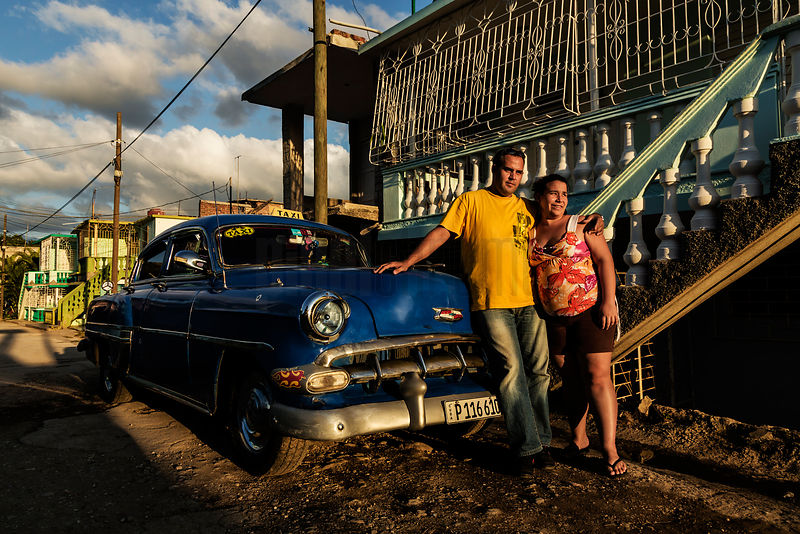 A Couple Standing Next to their Vintage American Chevrolet at Sunset