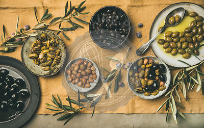 Flat-lay of Mediterranean pickled olives in plates and bowls