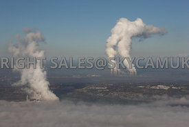 Power stations aerial photograph of the plumes of steam being vented by the Rocksavage power station in the foreground and Fiddlers Ferry in the background set against a clear blue sky with a thin layer of cloud in the foreground