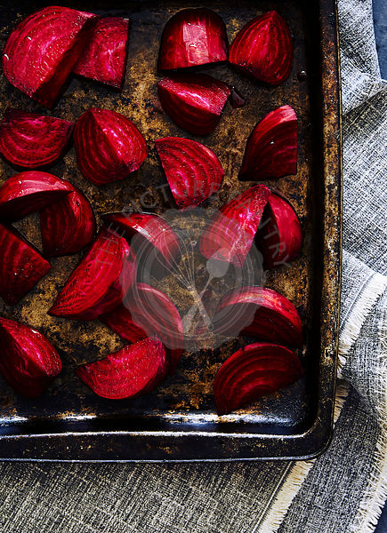raw cut beetroot on a dark rustic baking tray.