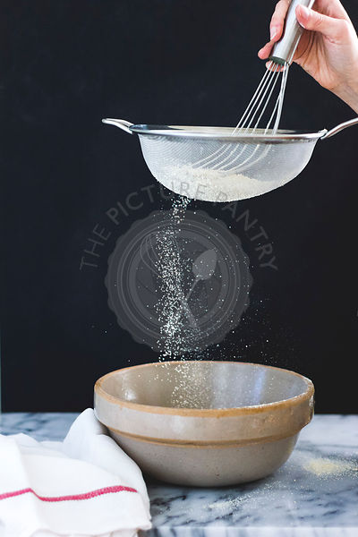 Sieving flower in to a mixing bowl.