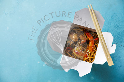 Udon noodles stir-fried with Tiger shrimps Asian food in box Take out food on blue background copy space