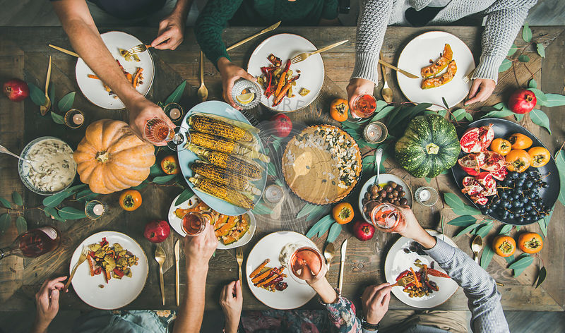 Friends eating and feasting at Thanksgiving Day with vegetarian meals