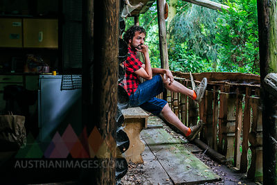 France, Strasbourg, pensive man sitting in old wooden hut