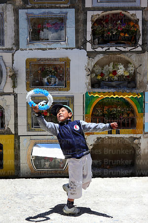 Boy playing with wreath in cemetery during Todos Santos festival, La Paz, Bolivia