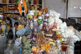 Woman selling chia, tunta and other spices on stall in San Pedro market, Cusco, Peru