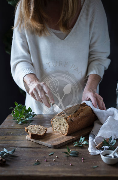 A woman slicing homemade bread in a kitchen