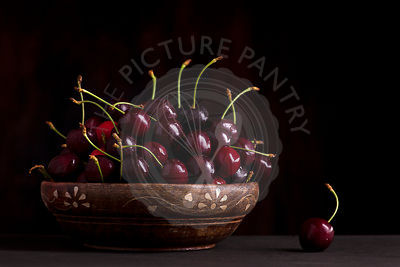 fresh cherries in bowl on wooden table