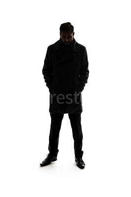 A silhouette of a mystery man in a big coat, standing and looking down – shot from eye level.
