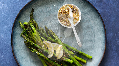 Chargrilled asparagus garnished with dukkah and lemon slices.