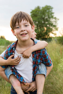 Portrait of smiling little boy giving his brother piggy back