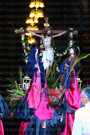 Penitents carrying statue of Jesus on the cross / Paso del Calvario out of La Merced church at start of Good Friday procession, La Paz, Bolivia