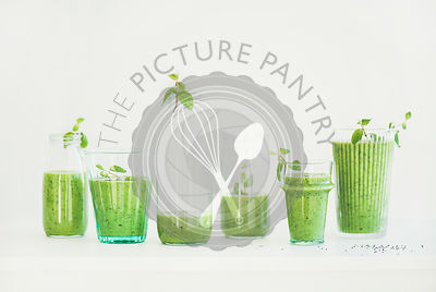 Matcha green smoothie with chia seeds in glasses, white background
